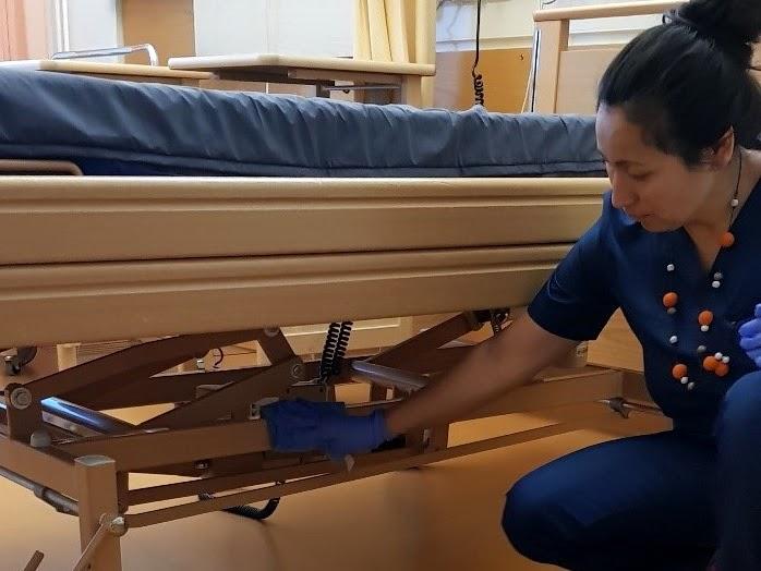Kuvassa laitoshuoltaja puhdistaa sairaalavuodetta pyyhkimällä